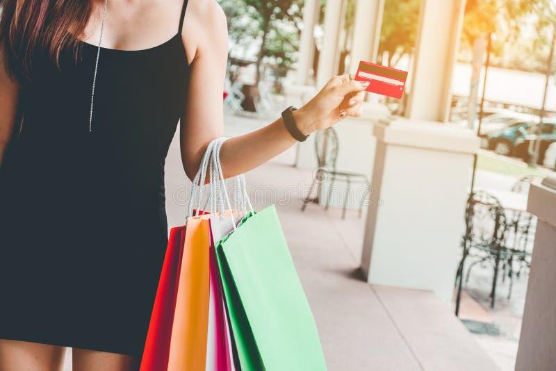 Femme tenant le crad de crédit appréciant la rue de achat photographie stock libre de droits