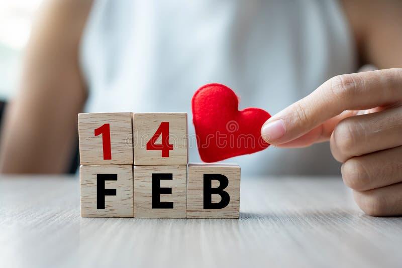 Femme tenant le cube en bois de coeur de forme en iwith rouge de décoration sur le fond de table Jour d'amour, de épouser, romant images stock