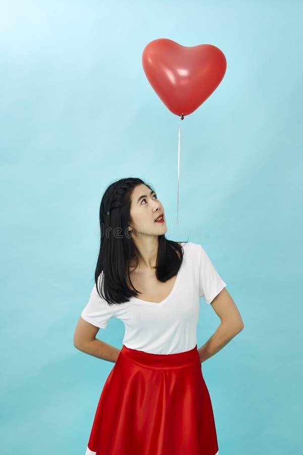Femme tenant le grand coeur rouge de ballon photo stock