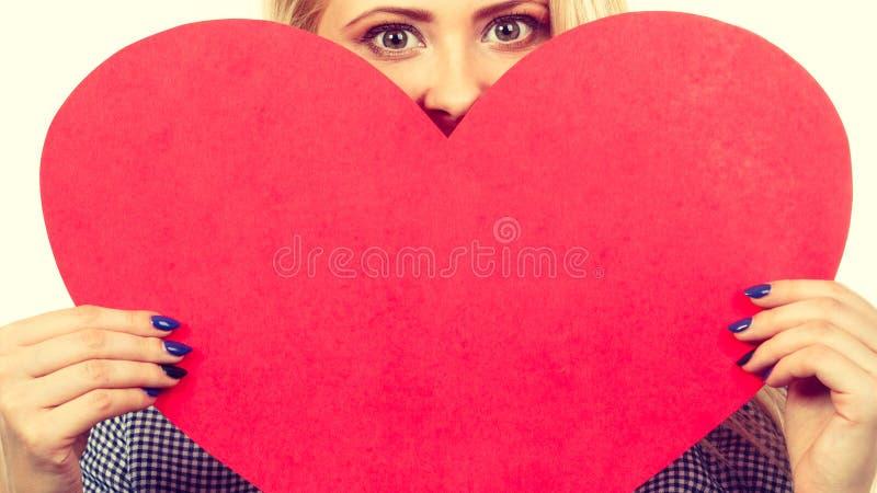 Femme tenant le grand coeur rouge, signe d'amour images libres de droits