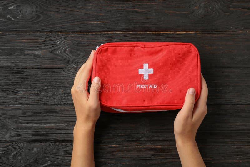 Femme tenant le kit de premiers secours sur la table foncée image stock