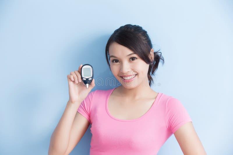 Femme tenant le mètre de glucose sanguin photographie stock libre de droits
