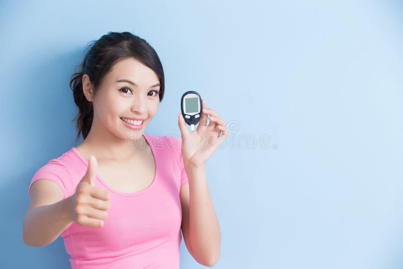 Femme tenant le mètre de glucose sanguin photos libres de droits