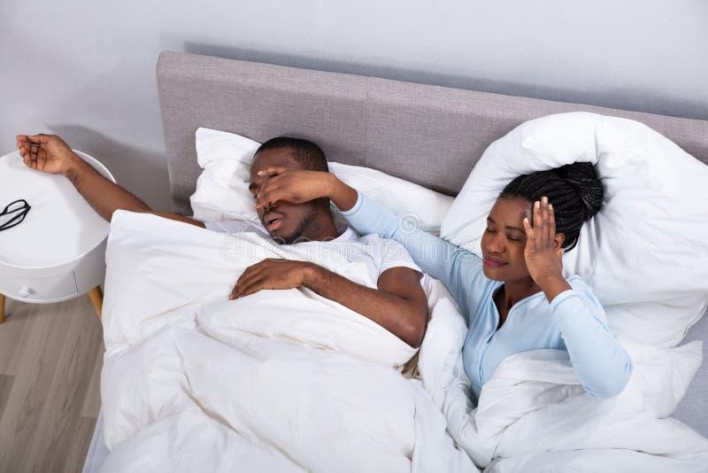 Femme tenant le nez de son mari pour l'arr?ter du ronflement images stock