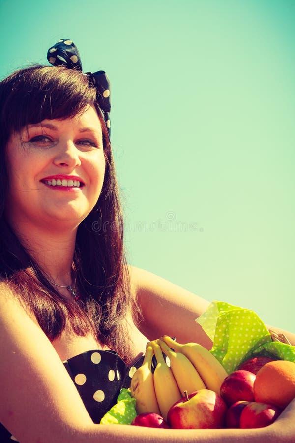 Femme tenant le panier de pique-nique avec des fruits images libres de droits
