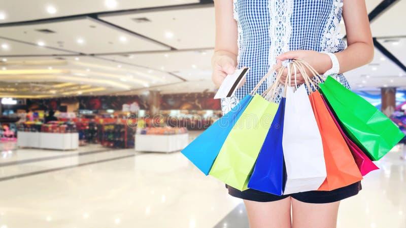 Femme tenant le panier et la carte de crédit dans le centre commercial photographie stock