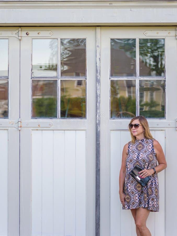Femme tenant le portefeuille noir se tenant devant la barre blanche rustique image libre de droits