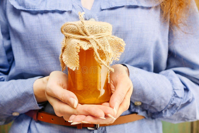 Femme tenant le pot en verre de miel photos stock