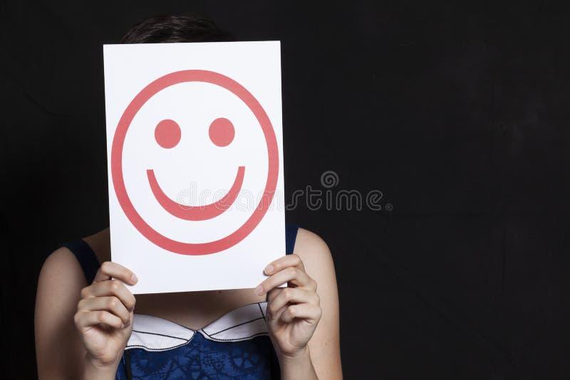 Femme tenant le sourire d'émoticône photo stock