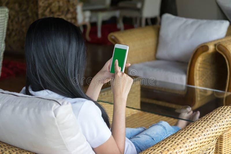 Femme tenant le téléphone intelligent mobile avec l'écran vert, FO sélectives image stock