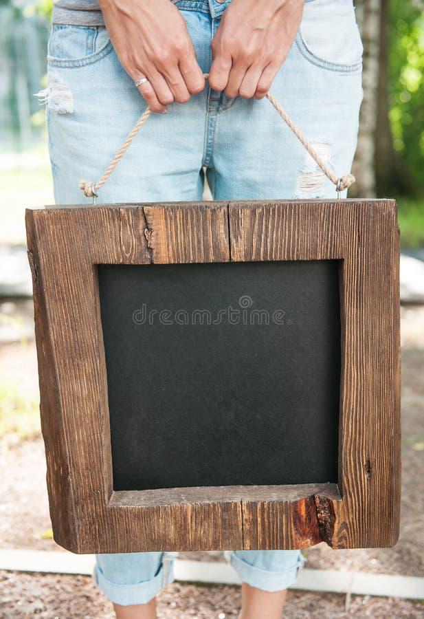 Femme tenant le tableau noir vide avec le cadre en bois Moquerie de calibre image libre de droits