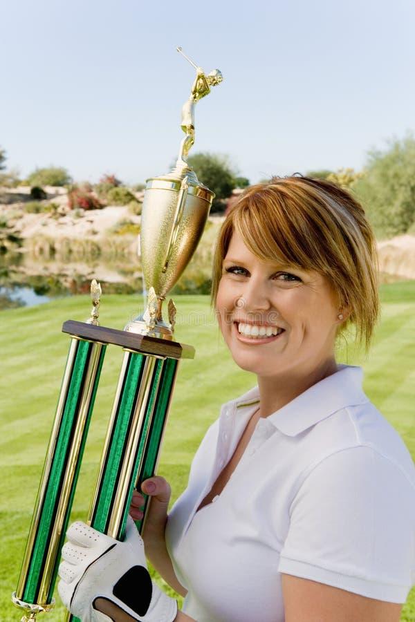 Femme tenant le trophée sur le terrain de golf images stock