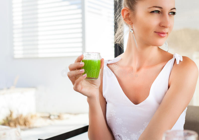Femme tenant le verre d'un jus vert dans sa main photographie stock libre de droits
