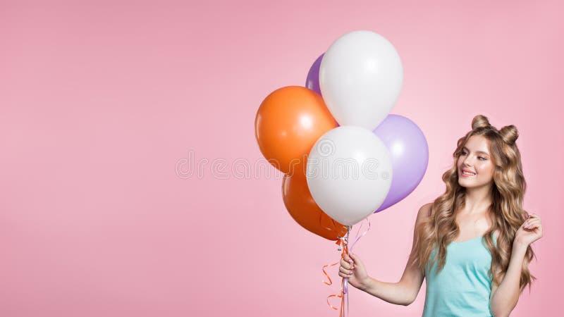 Femme tenant les ballons roses au-dessus du fond rose images stock