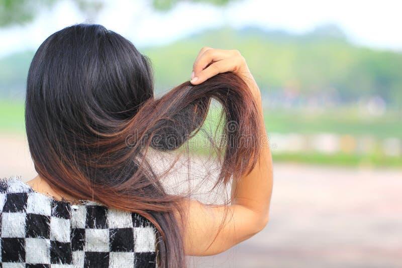 Femme tenant les cheveux secs endommagés malpropres dans des mains sur le fond de nature, concept de Haircare image stock