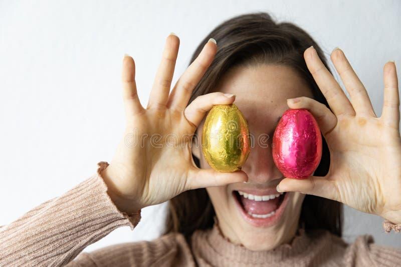 Femme tenant les oeufs de p?ques bleus et rouges de chocolat devant ses yeux photographie stock libre de droits