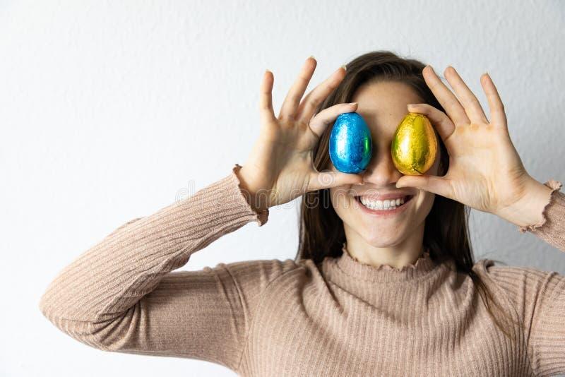Femme tenant les oeufs de p?ques bleus et d'or de chocolat devant ses yeux photo stock