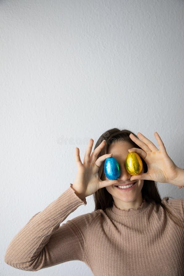Femme tenant les oeufs de p?ques bleus et d'or de chocolat devant ses yeux image stock