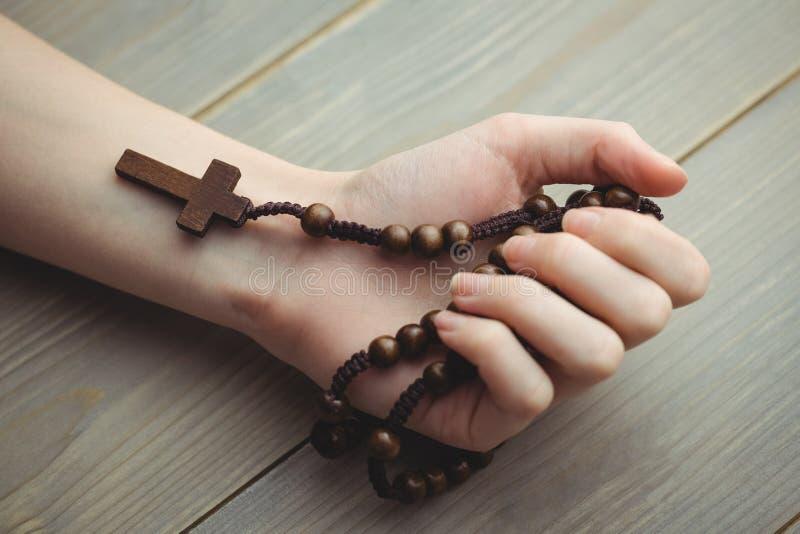Femme tenant les perles en bois de chapelet image libre de droits
