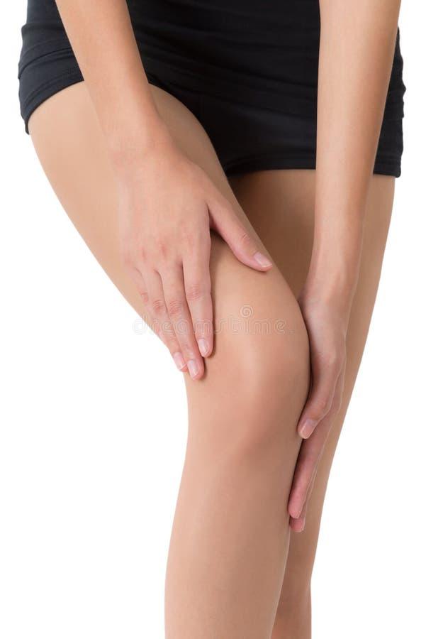 Femme tenant sa belle longue jambe saine avec masser le genou dans le secteur de douleur image libre de droits