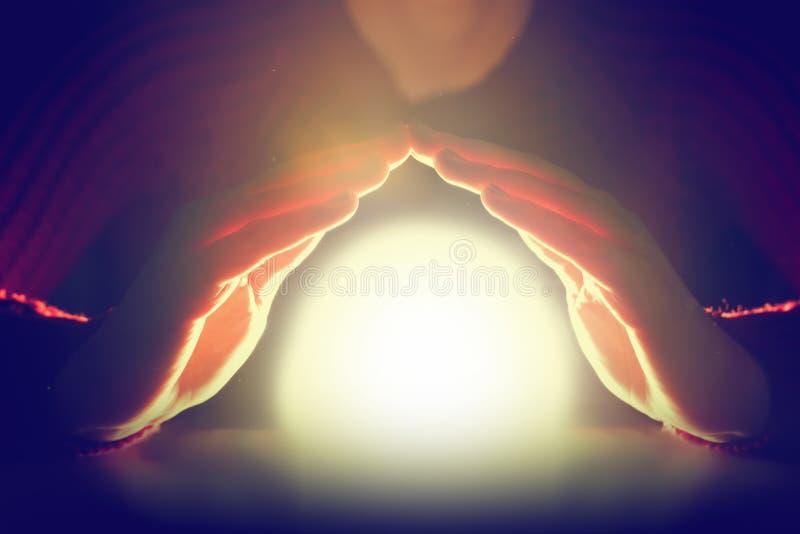 Femme tenant ses mains au-dessus de sphère rougeoyante de lumière Protection, avenir image stock