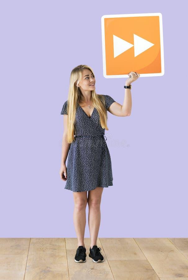 Femme tenant un bouton en avant rapide dans un studio photographie stock libre de droits