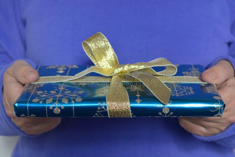 Femme tenant un cadeau admirablement enveloppé de Noël photo stock