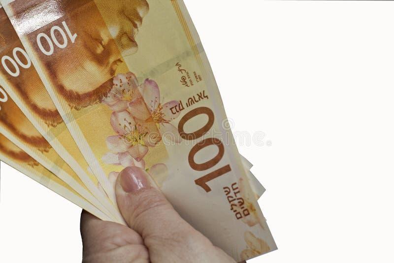 Femme tenant un groupe de nouveaux billets de banque israéliens de shekel photographie stock libre de droits