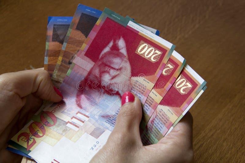 Femme tenant un groupe de nouveaux billets de banque israéliens de Sheqel dans son Han photographie stock