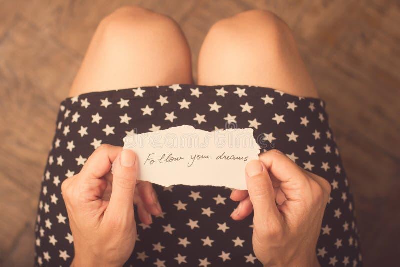 Femme tenant un morceau de papier avec un message photographie stock libre de droits