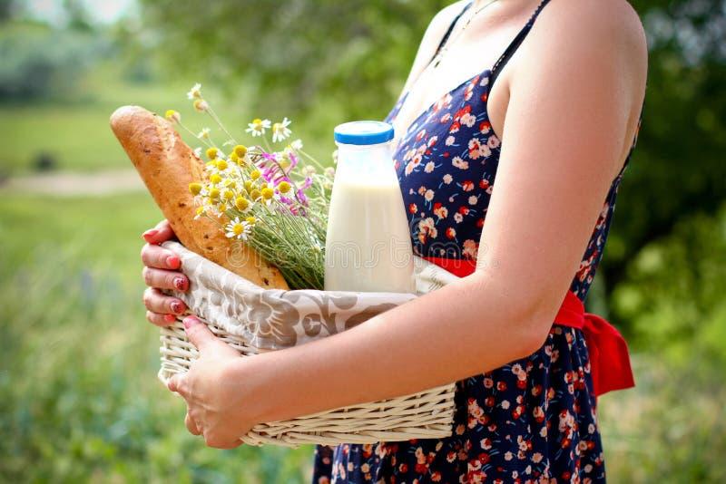 Femme tenant un panier avec du pain, le lait et des fleurs en été images libres de droits
