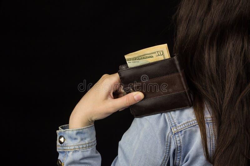 Femme tenant un portefeuille avec l'argent, plan rapproché, fond noir, billet de banque, dollars photo stock