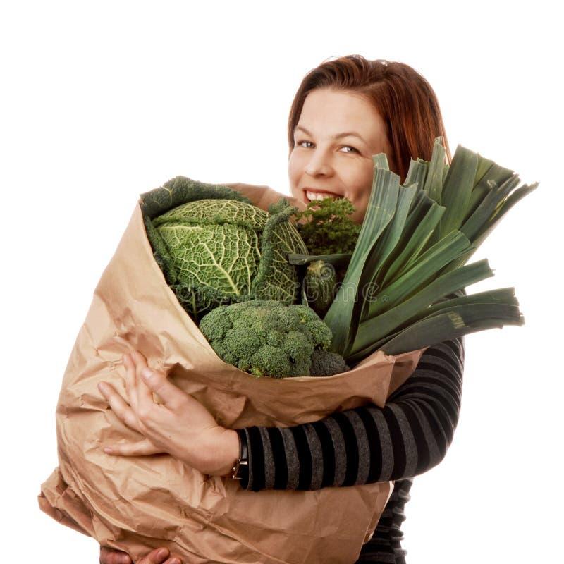 Femme tenant un sac à provisions de papier avec les légumes verts image libre de droits