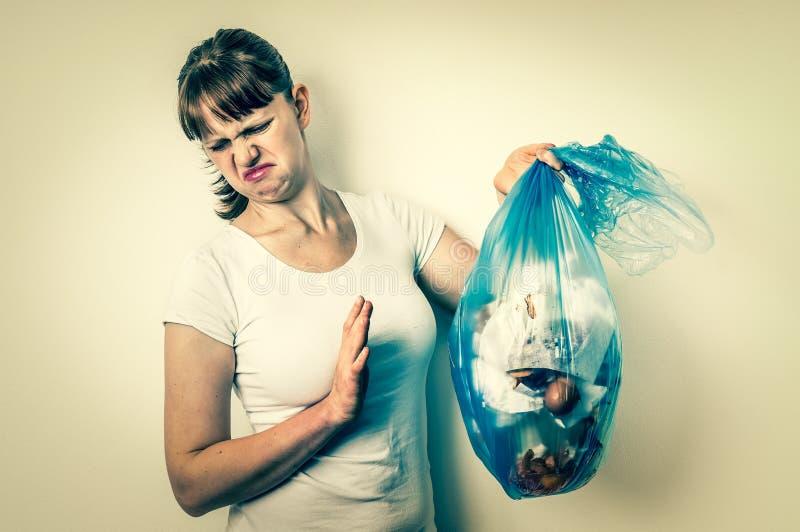Femme tenant un sac de déchets puant - rétro style image libre de droits