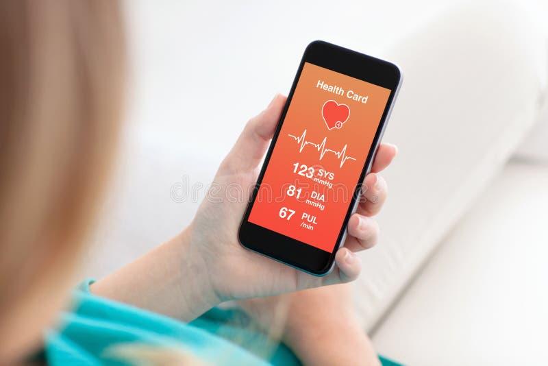 Femme tenant un téléphone avec l'APP pour la surveillance de carte de santé photo libre de droits