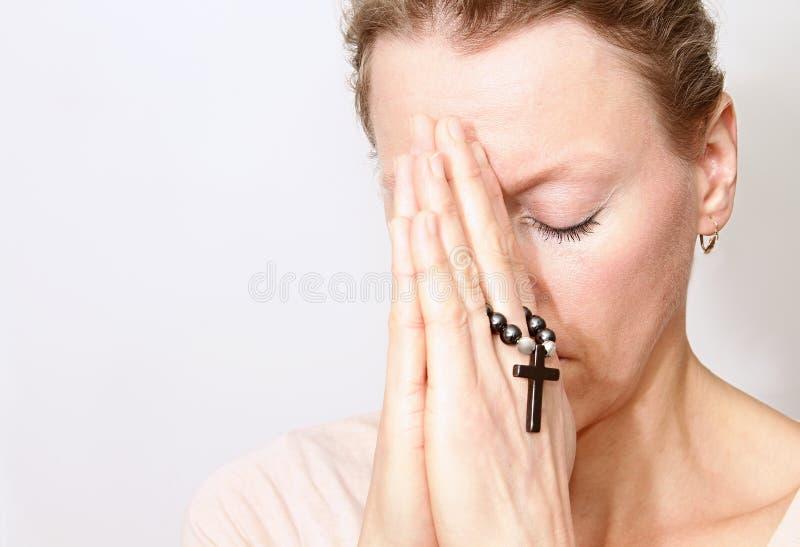 Femme tenant une croix et une prière photographie stock