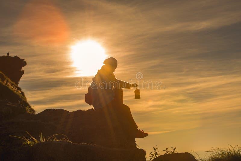 Femme tenant une lampe aérienne pour recevoir de l'énergie du soleil image libre de droits