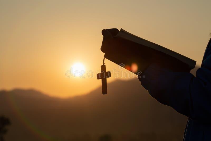 Femme tenant une Sainte Bible et une croix dans des ses mains et priant pendant le matin Mains pliées dans la prière sur une Sain image stock
