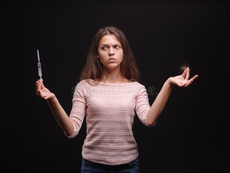 Femme tenant une seringue et une touffe des cheveux sur un fond noir Symptômes de dépendance et de maladie Concept de traitement  images stock