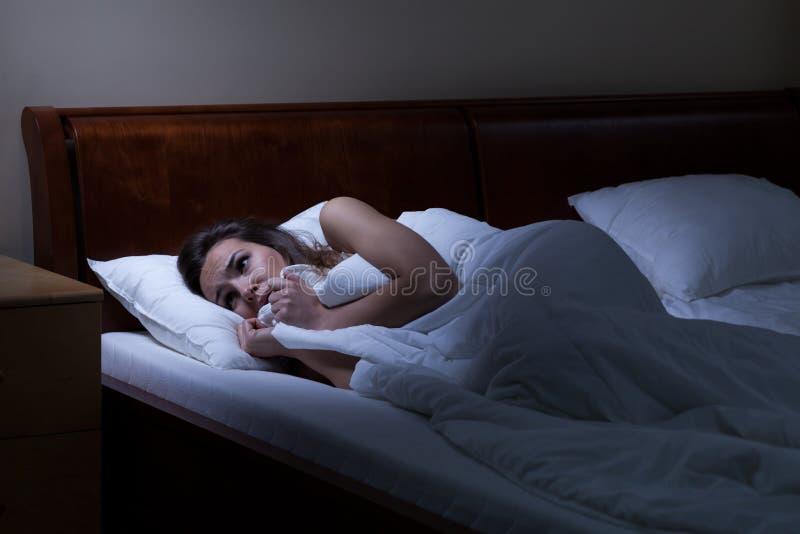Femme terrifiée se situant dans le lit photo libre de droits