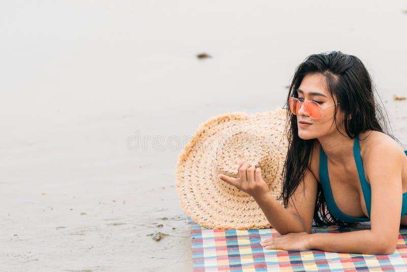 Femme thaïlandaise dans le bikini s'étendant sur le doigt de point de plage images stock