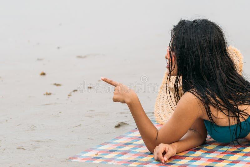 Femme thaïlandaise dans le bikini s'étendant sur le doigt de point de plage photographie stock libre de droits