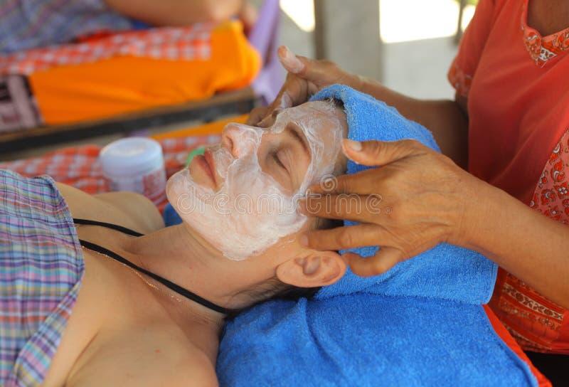 Femme thaïlandaise de massage de visage principal avec les yeux et les mains fermés de massage photographie stock