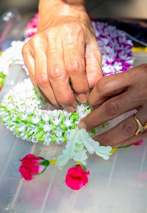 Femme tha?landaise faisant ? une tradition la guirlande tha?landaise de fleurs photos stock
