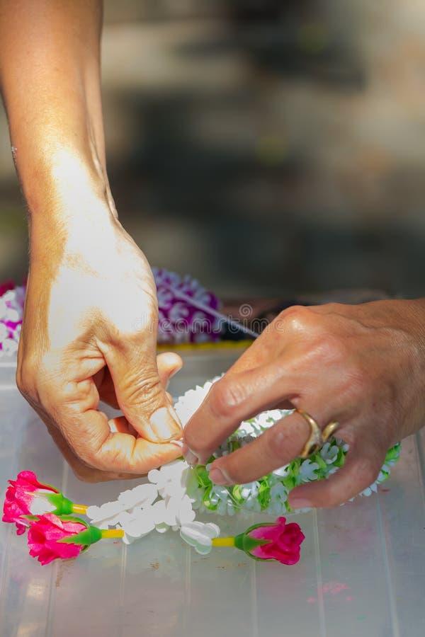 Femme tha?landaise faisant ? une tradition la guirlande tha?landaise de fleurs image libre de droits