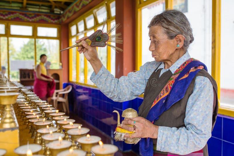 Femme tibétaine non identifiée priant dans le monastère bouddhiste de Tsuglagkhang, Gangtok, Sikkim, Inde photo stock