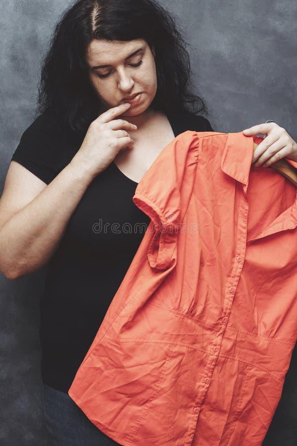 Femme timide obèse hésitant à utiliser la chemise vibrante images libres de droits