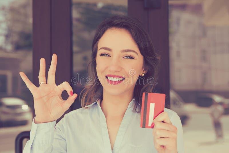 Femme Toothy de sourire tenant montrer la carte de crédit près du centre commercial de magasin de bureau dehors image libre de droits