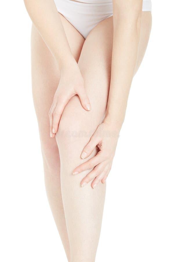 Femme touchant ses jambes et genou, chemin de coupure image libre de droits