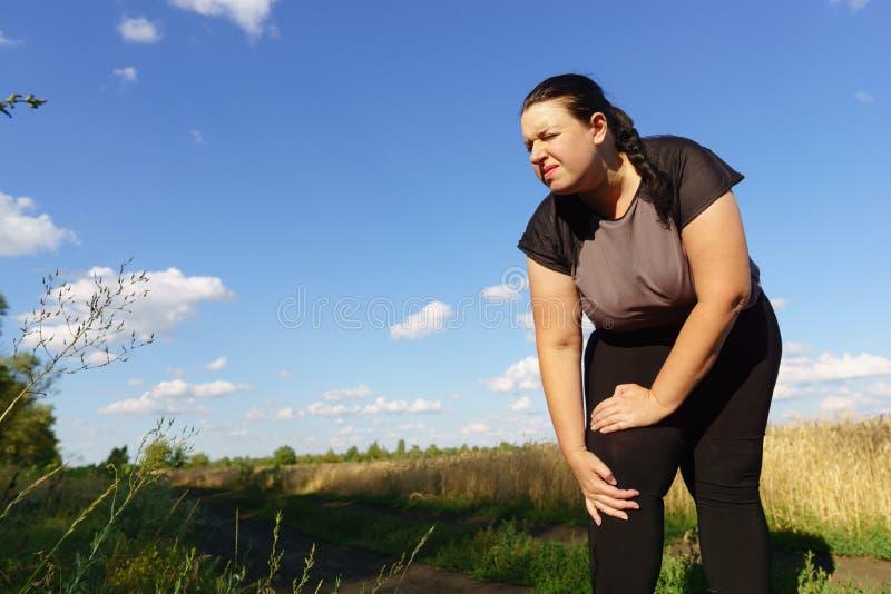 Femme touchant son genou, blessure de sports à pulser images stock